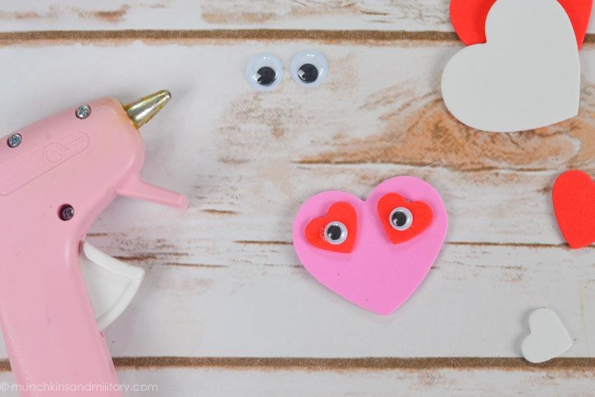 DIY Valentine's treat craft supplies - pink glue gun, googly eyes, pink and red foam hearts